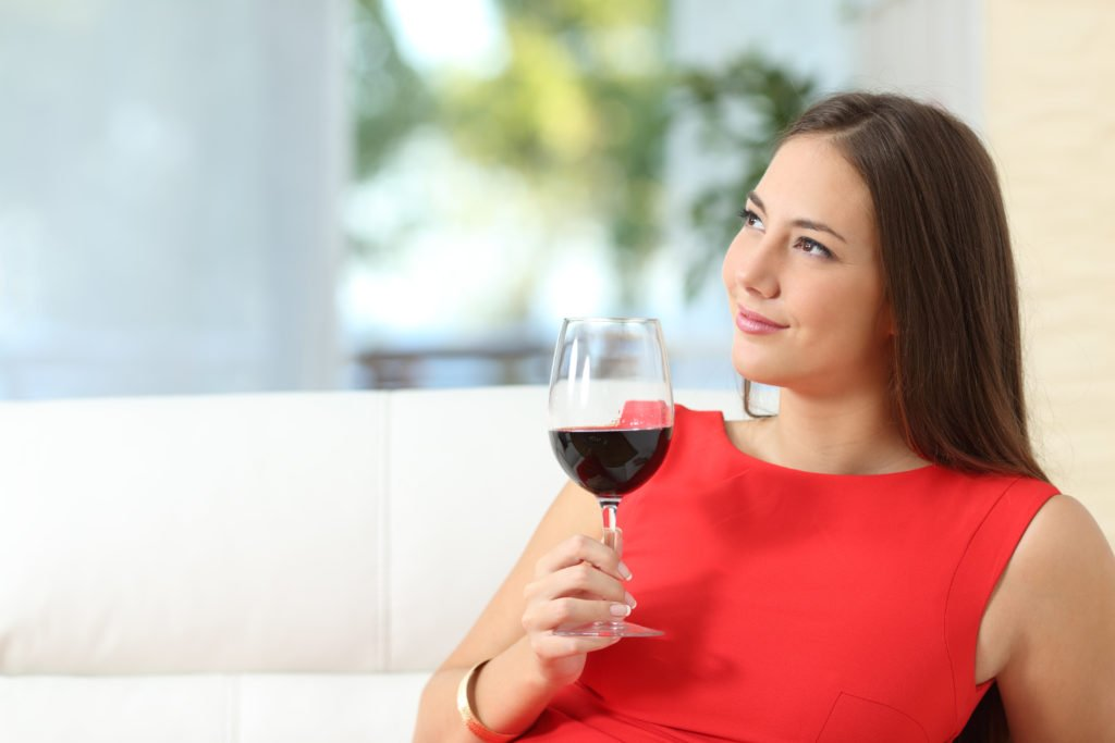 Pensive relaxed woman with a cup of wine
